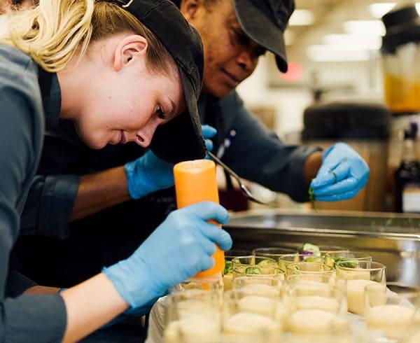 Zwei Mitarbeiter beim Anrichten eines Tellers