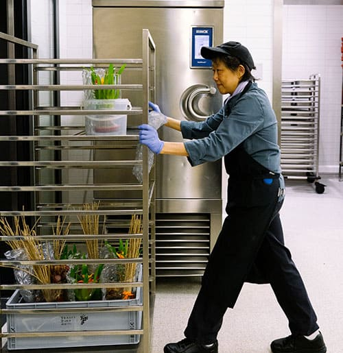 Mitarbeiterin beim Schieben eines Wagens in der Küche