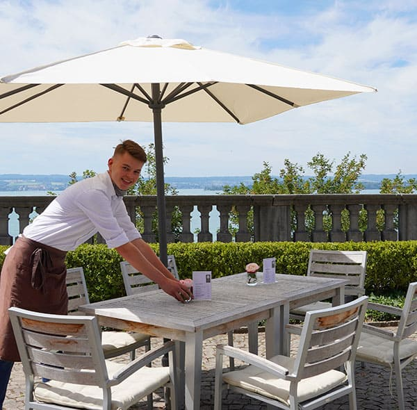 Service-Mitarbeiter dektoriert den Tisch im Außenbereich